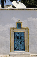 Tunisia, Sidi Bou Said.  Decorated Door of a Traditional House.  Blue and White are the Colors Traditionally Used in Sidi Bou Said.  Satelite Dish on Roof.