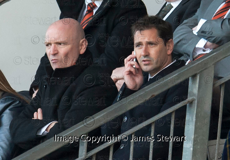 Dundee Utd Chairman Steven Thompson doesn't look too happy as manager Jackie McNamara tries to get his instructions to the bench by mobile phone.