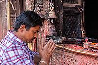 Nepal, Patan.  Worshiper Asking for a Blessing at a Hindu Temple.
