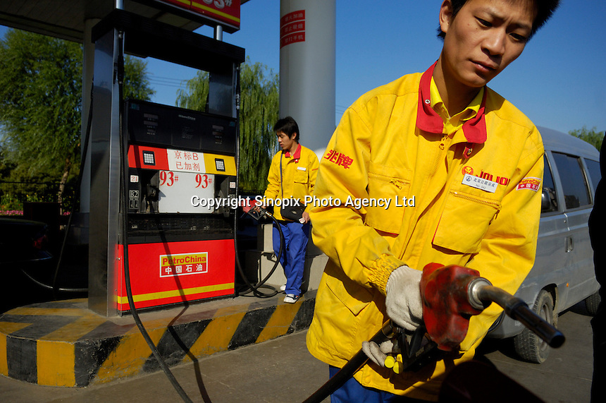 Petrol pump attendants in a gas station of PetroChina in Beijing, China. PetroChina is one of China's main oil and gas producers which owns 17,400 gas stations in China and now expanding internationally..
