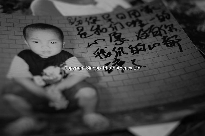 """Picture of a little boy, Li Yuan Hu, 4 years old, lost in GuanDu district in Kumming city on 25 November 2004. Message written by Mrs Li reads """"Our only wish is to see you come home as soon as possible. Our hearts are broken without you.""""..PHOTO BY SINOPIX"""