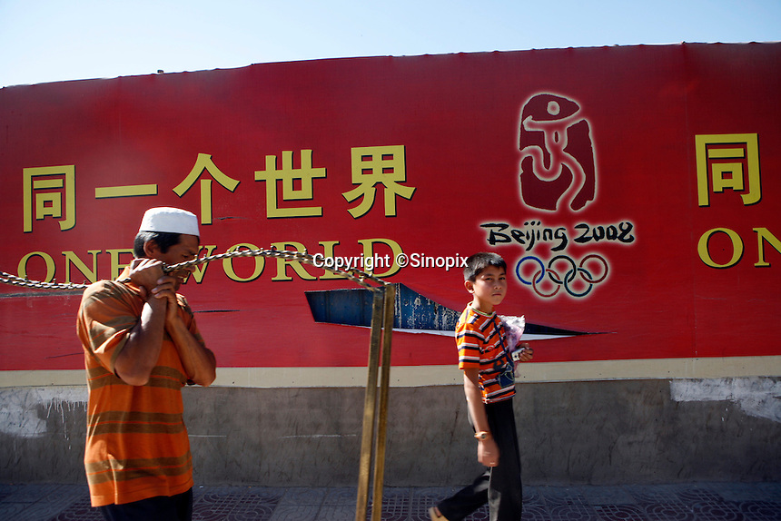 """Local Uihgur pass a """"One World One Dream"""" slogan of the Beijing Olympic Games in Kashgar, China. An attack happened in Kashgar yesterday killed 16 police.."""