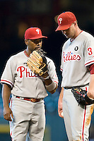 Philadelphia Phillies shortstop Jimmy Rollins #11 chats with pitcher Roy Halladay #34 during the Major League Baseball game against the Houston Astros at Minute Maid Park in Houston, Texas on September 14, 2011. Philadelphia defeated Houston 1-0 to clinch a playoff berth.  (Andrew Woolley/Four Seam Images)