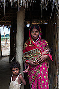 25 year old Sri Kanthi Devi poses for a photograph with her children, 3 year old Chandni and her 3 months old son, Chandan Kumar in her house in Ramgarwa village in Raxaul district in Bihar, India.