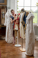 BNPS.co.uk (01202) 558833<br /> Pic: ZacharyCulpin/BNPS<br /> <br /> Pictured: Artist Stephanie Smart with the incredible paper outfits. (From left) A Regency 'walking dress' complete with a high necked spencer jacket, a coat inspired by Napoleon an early 19th century British naval uniform and a another Regency walking dress<br /> <br /> A textile artist has unveiled a collection of remarkable Regency outfits she has painstakingly made out of paper.<br /> <br /> Stephanie Smart has produced 11 life-sized outfits including a red frockcoat modelled on the style of Napoleon.<br /> <br /> Others depict walking dresses, naval uniforms and spencer jackets from the Regency era. (1795-1837)<br /> <br /> Her creations are on display as part of an exhibition titled The Regency Wardrobe at Firlie Place in East Sussex.