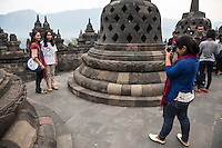 Borobudur, Java, Indonesia.  Tourist Taking Friends' Picture.