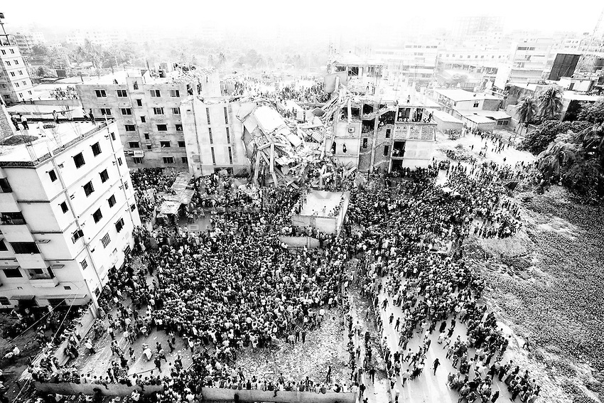 Crowds gather at the collapsed Rana Plaza building as people rescue garment workers trapped in the rubble. Shavar. near Dhaka, Bangladesh
