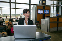 Happy business woman using laptop pc computer while sitting in departure lounge at the Austin International Airport. Horizontal shot.
