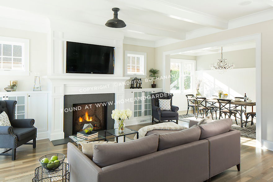 Fireplace, built-in bookshelves, and box beam ceiling in the living room of a traditional home.