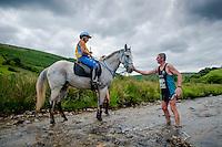 Saturday 14 June 2014<br /> Pictured: Runners and riders make their way through the course at the 35th man V Horse event at LLanwrtyd Wells <br /> Re:  Man v Horse Marathon takes place at Llanwrtyd Wells, Powys. Runners and riders are pitted head to head acrros a marathon course to see who is the fastest.