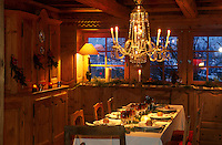 This panelled dining room is lit by an elegant chandelier and is laid for a Christmas meal