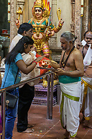 Worshiper Seeking Blessing from Hindu Priest Holding Ceremonial Fire, Hindu Temple Sri Vadapathira Kaliammam during Navarathiri Celebrations, Singapore.