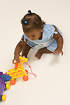 8 month old baby girl sitting leaning over to examine toy horizontal