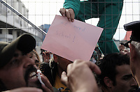 "Pictured: A young boy with a ""We Need School"" placard on top of the fence of the camp Monday 06 February 2017<br /> Re: Scuffles between migrants and police broke out during a visit by Immigration Policy Minister Yiannis Mouzalas at the Elliniko migrant camp located in the former airport in the outskirts of Athens, Greece."