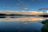 The landscape around Kolob Reservoir are reflected in its calm waters in Southern Utah