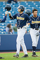 Christian Wolfe (21) of the UNCG Spartans celebrates with teammates after hitting a 2-run home run against the Georgia Southern Eagles at UNCG Baseball Stadium on March 29, 2013 in Greensboro, North Carolina.  The Spartans defeated the Eagles 5-4.  (Brian Westerholt/Four Seam Images)