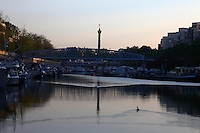 Paris Right Bank: A view of the port de l'Arsenal in Paris (it links the Canal de Saint Martin to place de la Bastille), with its boats, its typical bridge, and the column of July that reflects itself onto the basin water on the background, in the sunrise light. The water surface is slightly rippled by some ducks, the profile of one of which stands out.<br /> <br /> You can download this file for (E&PU) only, but you can find in the collection the same one available instead for (Adv).