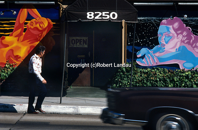 Man walking past a brightly painted panels outside of the Body Shop strip club on Sunset Bvld. in Los Angeles