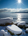 Idaho, North, Sandpoint. Winter sun over Lake Pend Oreille with snow covered lakeshore boulders.