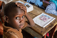 Senegal, Touba.  Young Boy at Al-Azhar Madrasa, a School for Islamic Studies.  His book shows that he is learning Arabic.