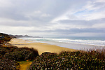 U.S. Highway 101, Pacific Coast Scenic Byway, near Depot Bay, Oregon.  Oregon Central Coast, beaches, bays, bars, family fun, winter storms, lighthouses, fishing boats, bluffs, fossils and beach walks.  Yaquina Head and Yaquina Lighthouse in background.
