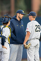 Michigan Wolverines pitching coach talks with pitcher Blake Beers (29 and catcher Casey Buckley (24) on the mound during the NCAA baseball game against the Eastern Michigan Eagles on May 8, 2019 at Ray Fisher Stadium in Ann Arbor, Michigan. Michigan defeated Eastern Michigan 10-1. (Andrew Woolley/Four Seam Images)