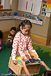Education preschoool children ages 3-5 jobs classroom chores girl collecting picture books before start of circle time vertical