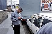 Neighbourhood Warden employed by Tower Hamlets Council inspects a dumped car in Bethnal Green.