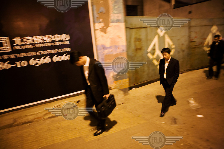 City workers walking home after work pass a construction site with a billboard poster advertising a new shopping mall opening in the city.