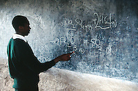 Kenya. Rift Valley Province. Nyahururu. Classroom at Munyaka secondary school. A student writes on the blackboard the answers to a chemistry problem. The boy is wearing a green uniform. © 2004 Didier Ruef