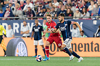 FOXBOROUGH, MA - AUGUST 25: Carles Gil #22 of New England Revolution dribbles  as Djordje Mihailovic #14 of Chicago Fire defends during a game between Chicago Fire and New England Revolution at Gillette Stadium on August 24, 2019 in Foxborough, Massachusetts.