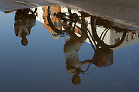 Reflection of two people riding bicycles in a puddle on the street, Datong, Shanxi, China.