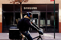 NEW YORK, NEW YORK - MARCH 04: A man rides his bike in front Samsung 837 store on March 04, 2021 in New York. Samsung Electronics Co Ltd is considering four sites en United States, for a new $17 billion chip plant. (Photo by Emaz/VIEWpress)
