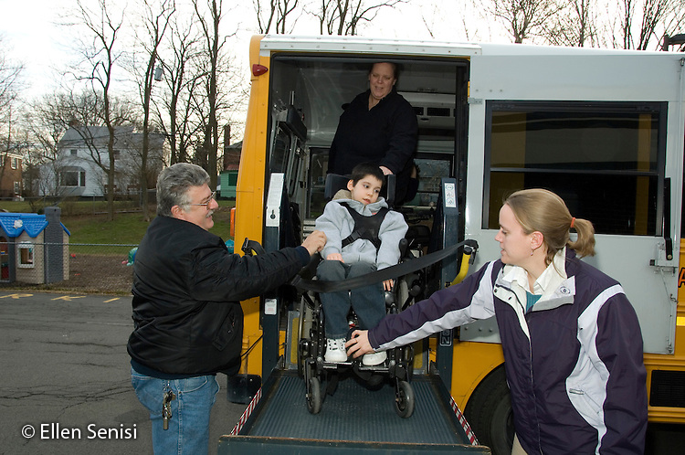 MR / Albany, NY.Langan School at Center for Disability Services .Ungraded private school which serves individuals with multiple disabilities.Child boards schoolbus using wheelchair lift operated by bus driver while teacher adjusts footrest. Boy: 8, cerebral palsy, spastic quadriplegic, nonverbal with expressive and receptive language delays.MR: AH-cfds, Hac2.© Ellen B. Senisi