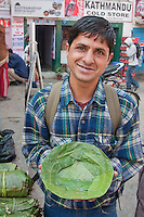 Kathmandu, Nepal.  A Nepali Man, a Brahmin, Shows a Machine-made Bowl of Sal Leaves, used to place food offerings at shrines and temples.