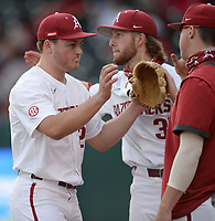 Arkansas starter Kole Ramage is congratulated by teammates Tuesday, April 6, 2021, as he returns to the dugout after the third out of the top of the first inning of play against UALR at Baum-Walker Stadium in Fayetteville. Visit nwaonline.com/210407Daily/ for today's photo gallery. <br /> (NWA Democrat-Gazette/Andy Shupe)