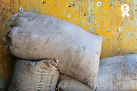 Construction rubbles in bags by yellow wall (Licence this image exclusively with Getty: http://www.gettyimages.com/detail/83676011 )