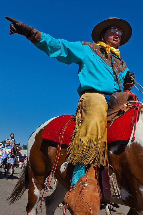 A rider motions to direct the contestants in the parade.
