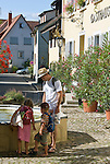 Germany, Baden-Wuerttemberg, Markgraefler Land, wine village Britzingen, centre with fountain, kids playing with water