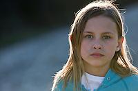 Young blonde girl at edge of lake.