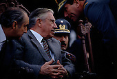 """Talca, Chile<br /> September 1988<br /> <br /> General Augusto Pinochet and his advisors.<br /> <br /> In October 1988, General Pinochet ordered a plebiscite vote asking Chilean citizens whether he should continue in office. It produced a decisive """"no"""" vote and the following year he lost the first presidential election in 19 years. However, under a constitution crafted by his advisors, he remained as army commander until 1998. <br /> <br /> Pinochet continued to wield enormous power until his arrest in London on human rights charges in October 1998."""