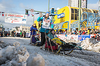 Anna Berington and team leave the ceremonial start line with an Iditarider at 4th Avenue and D street in downtown Anchorage, Alaska during the 2015 Iditarod race. Photo by Jim Kohl/IditarodPhotos.com