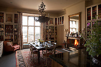 An informal dining room lined with bookcases. Note the distinctive wall lights which also surround the room