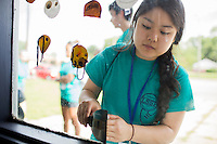 """Lina Ding scrapes paint off of a window in an entryway during """"Circle the City with Service,"""" the Kiwanis Circle K International's 2015 Large Scale Service Project, on Wednesday, June 24, 2015, at the Friendship Westside Center for Excellence in Indianapolis. (Photo by James Brosher)"""
