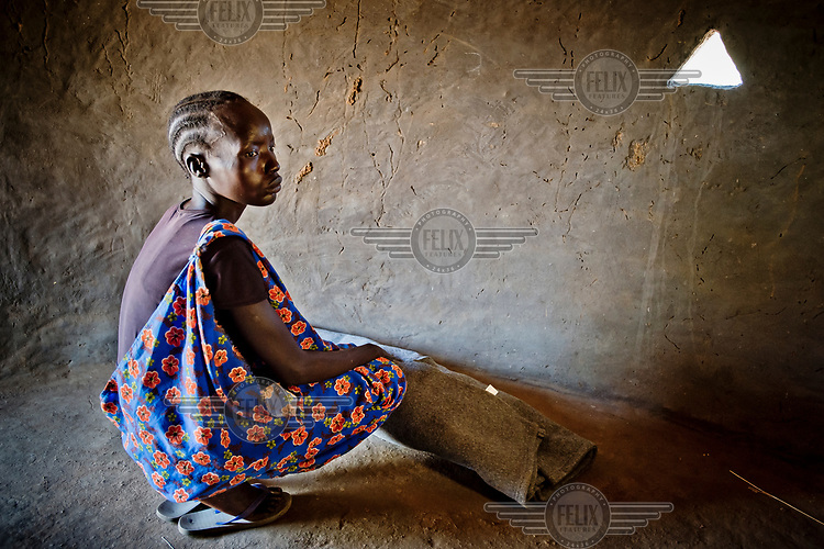 A woman squats next to the corpse of a three week old baby, wrapped in an UNHCR blanket, who died in the night at the Dzaipi health clinic. The baby's mother is too sick to attend so her co-wife is burying the unnamed child in Olua South Sudanese refugees' settlement.