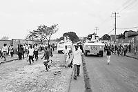 Haitians walking through the street chanting political slogans as UN armored vehicles drive through.