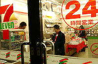 A lady buys groceries at a 7-11 convenience store in Kumegawa, Tokyo. The 24 hour American franchaise shop is a success in Japan..