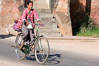 Myanmar, Burma.  Bagan.  Woman on Bicycle.
