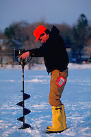 Man drilling a hole in the ice for ice fishing; his fishing license is visible.