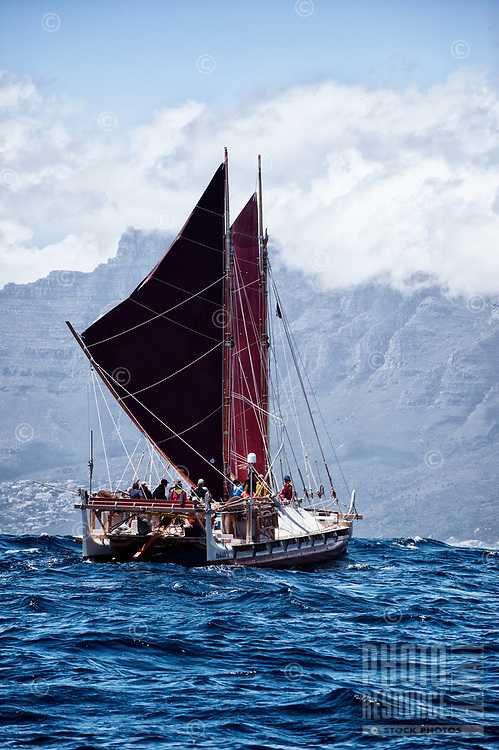 """Voyaging canoe Hokule'a nears Cape Town, with Twelve Apostles (peaks in the distance), South Africa, November 12, 2015; en route between Hout Bay and Cape Town (sailing from Simon's Town). Hokule'a was on a """"Malama Honua"""" (Care for the Earth) worldwide voyage to raise awareness about the importance of protecting the world's oceans, considered the greatest environmental challenge of our time."""